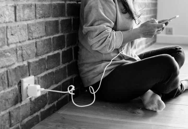 grayscale photography of person using smartphone while charging