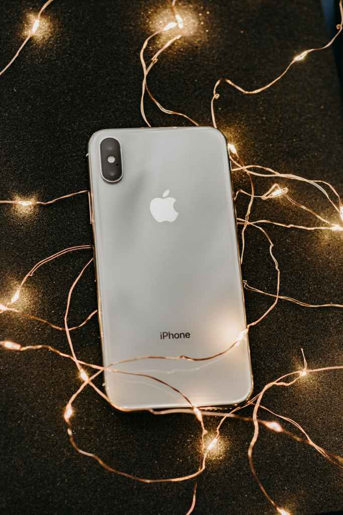 silver iphone x lying on pre lit string lights